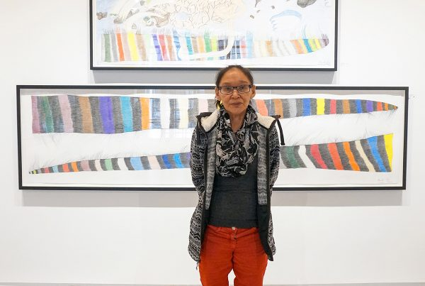 Photo of Shuvinai Ashoona in a gallery in front of two of her works on paper